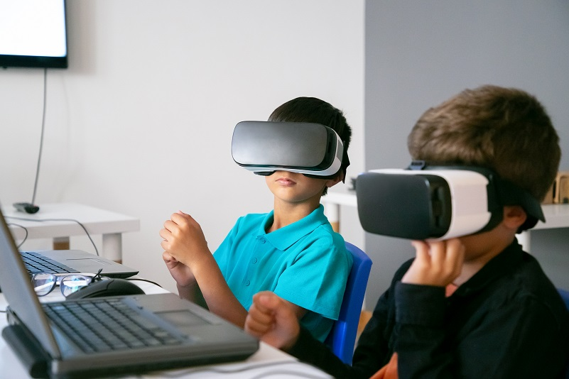 Little boys using VR headset and sitting at table
